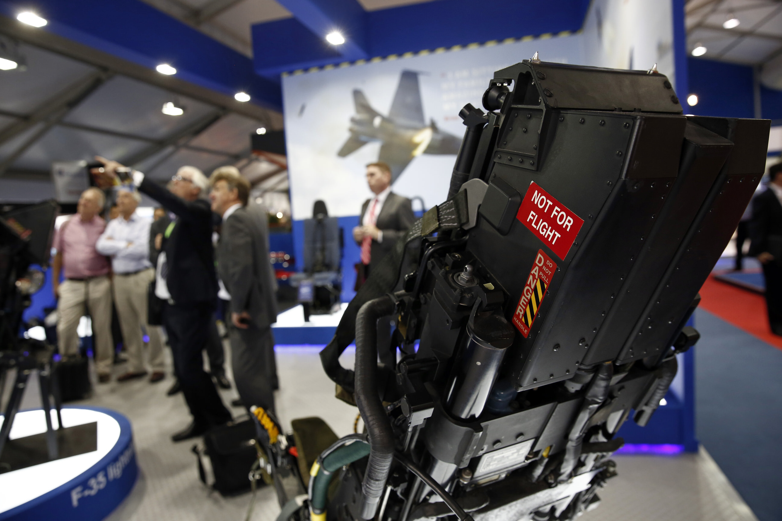 A 'Not For Flight' warning sticker sits on the side of an ejector seat, used in the Lockheed Martin Corp. F-35 Lightning II joint strike fighter jet, as it stands on display on the second day of the Farnborough International Airshow in Farnborough, U.K., on Tuesday, July 15, 2014. Photographer: Simon Dawson/Bloomberg