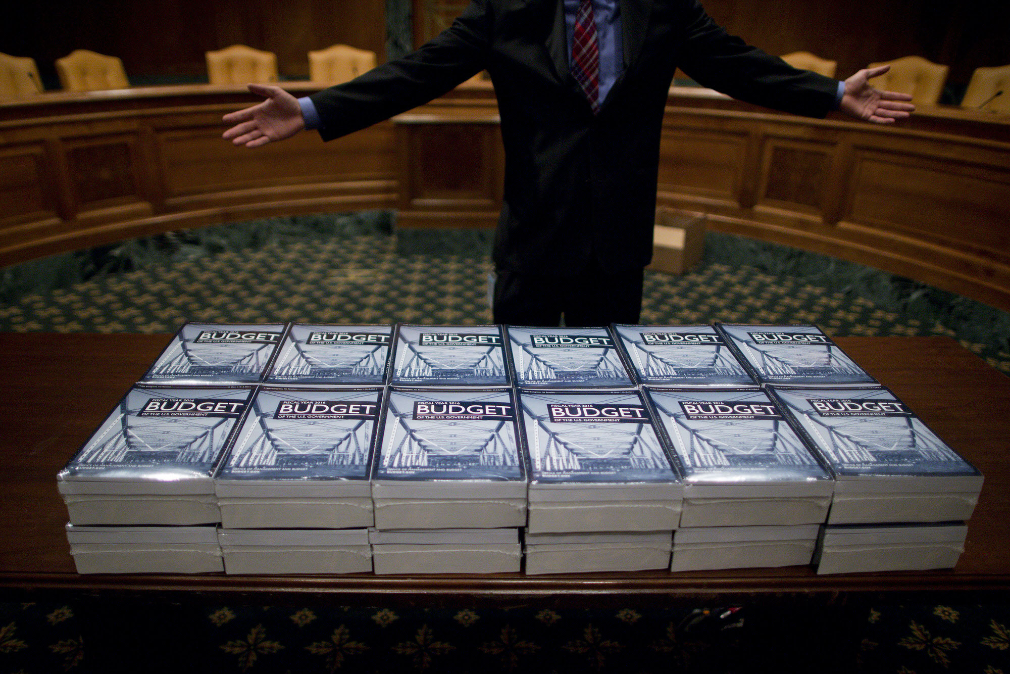 Eric Chalmers, staff assistant with the Senate Budget Committee, gestures while talking to a staff member behind copies of U.S. President Barack Obama's Fiscal Year 2016 Budget arranged on a table at the Senate Budget Committee hearing room in Washington, D.C., U.S., on Monday, Feb. 2, 2015. Photographer: Andrew Harrer/Bloomberg