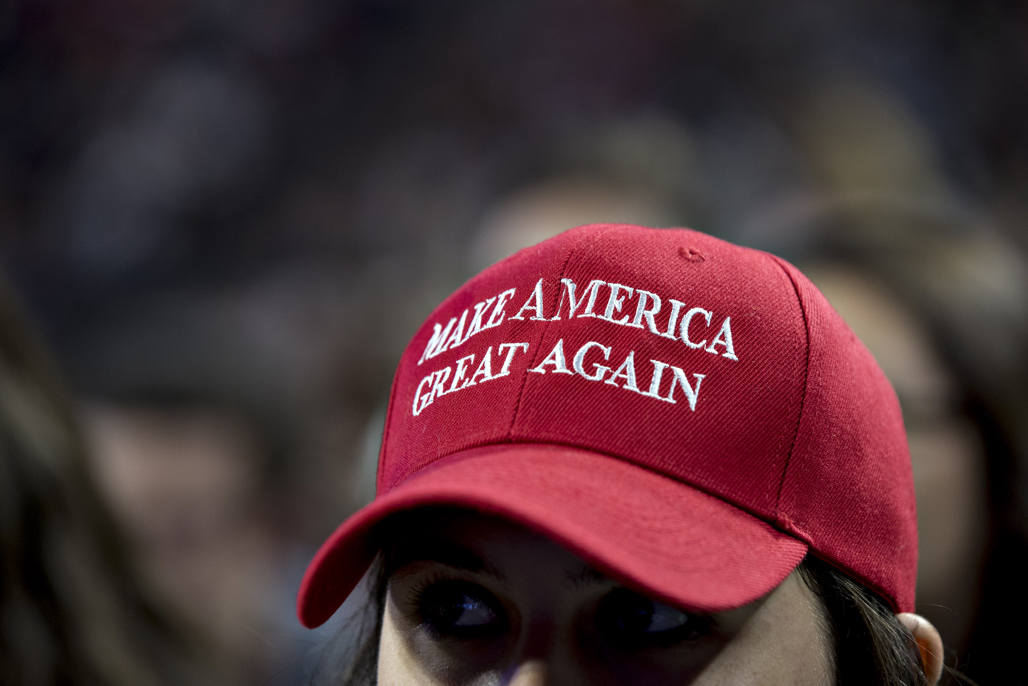 "A student wears a ""Make America Great Again"" campaign as Mike Pence, 2016 Republican vice presidential nominee, not pictured, speaks at a Liberty University Convocation in Lynchburg, Virginia, U.S., on Wednesday, Oct. 12, 2016. Indiana Governor Pence ended speculation Monday that he would leave the ticket, praising his running mate Donald Trump's performance in the debate with Democratic opponent Hillary Clinton on Sunday night. Photographer: Andrew Harrer/Bloomberg"
