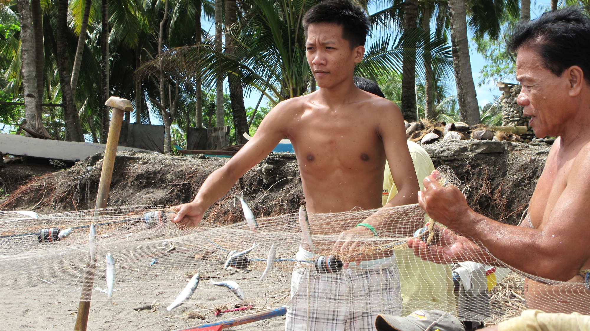 Fishers in Amlan, Philippines haul in their catch.