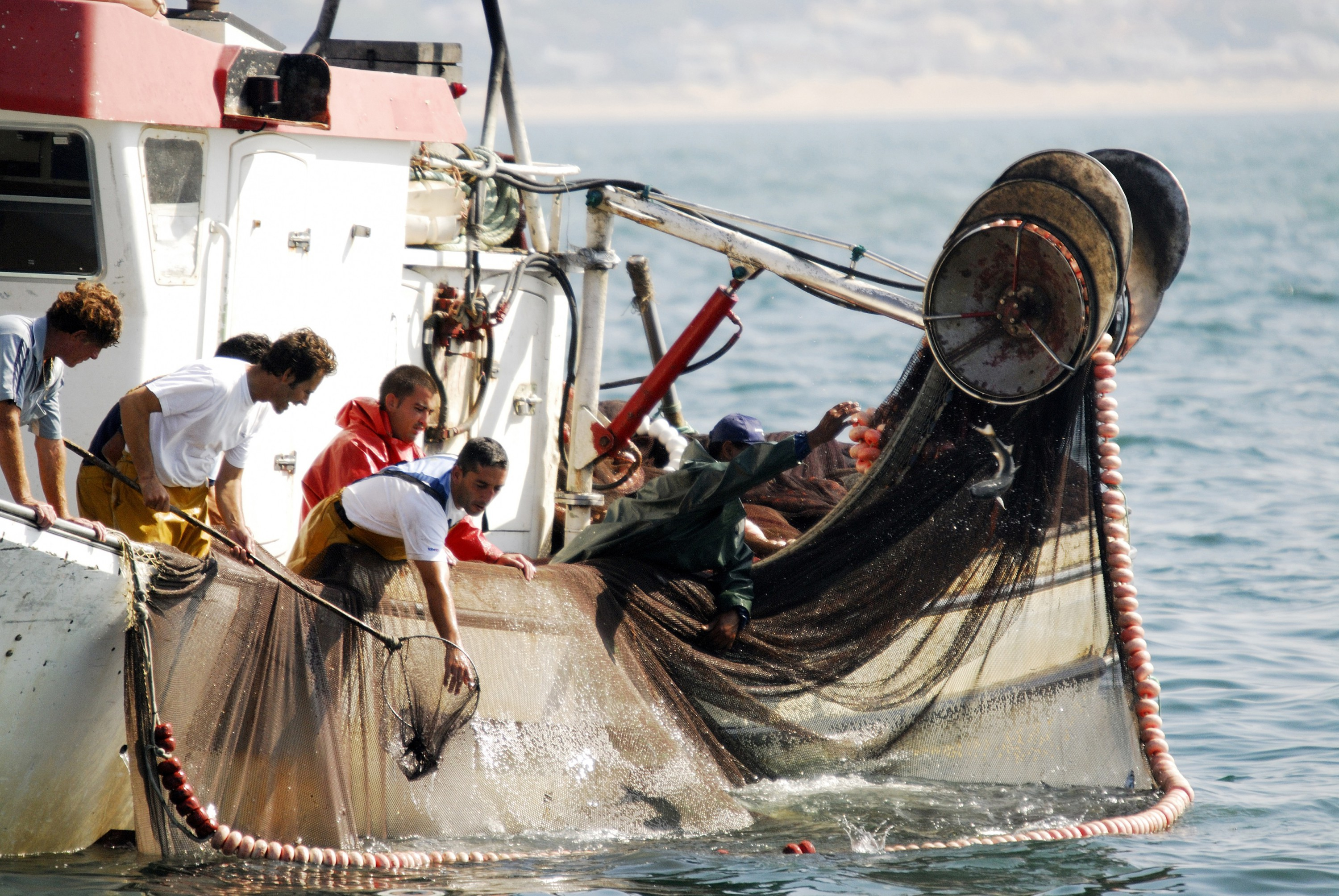 Fishermen rolling up their nets in Huelva, Spain.