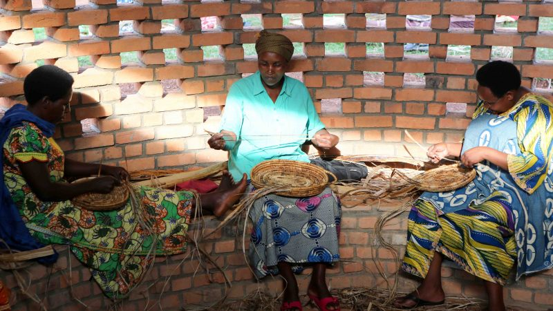 Three graduates of Women for Women International's training and education program sit in one of six classrooms found on the environmentally sustainable campus of the Women's Opportunity Center, where they weave baskets that are being sold at the Kigali Marriott Hotel, Macy's and at the facility's shop.