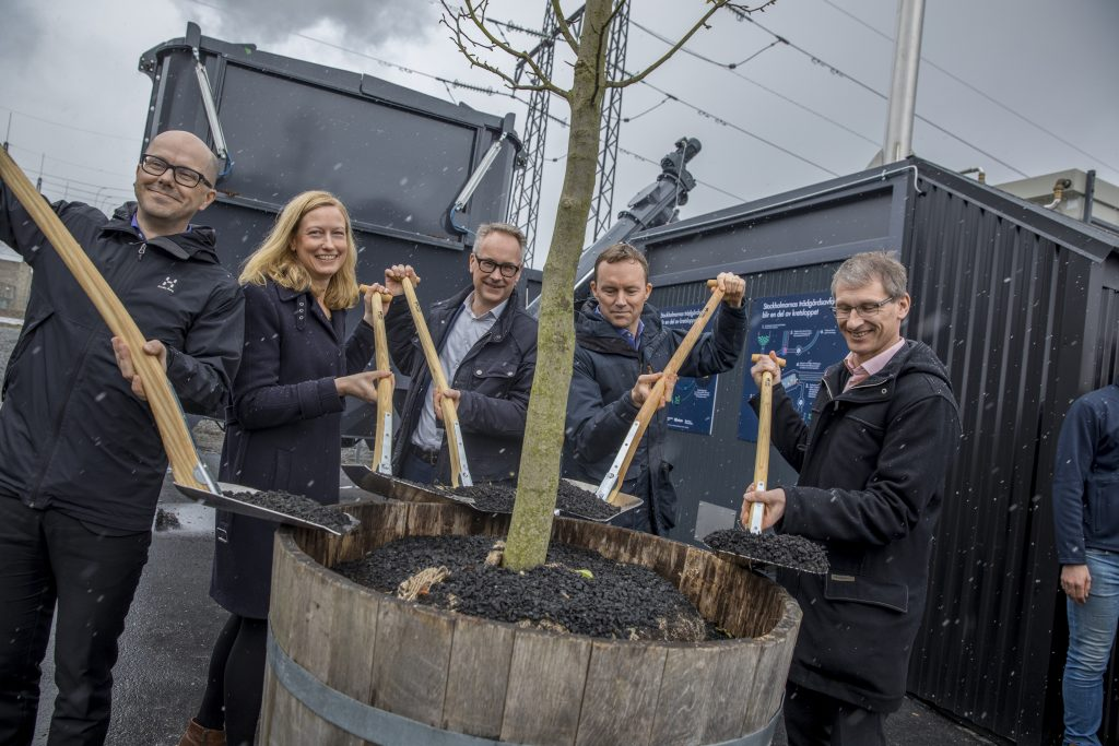 Jonas Eliasson, Head of Traffic Department, City of Stockholm, Katarina Luhr, Vice Mayor of Environment, City of Stockholm in Stockholm, Krister Schultz, CEO, Stockholm Water, James Anderson, Government Innovation, Bloomberg Philanthropies, and Anders Egelrud, CEO, Fortum Värme shovels biochar from a wheelbarrow to add to a newly planted tree. Credit: Casper Hedberg