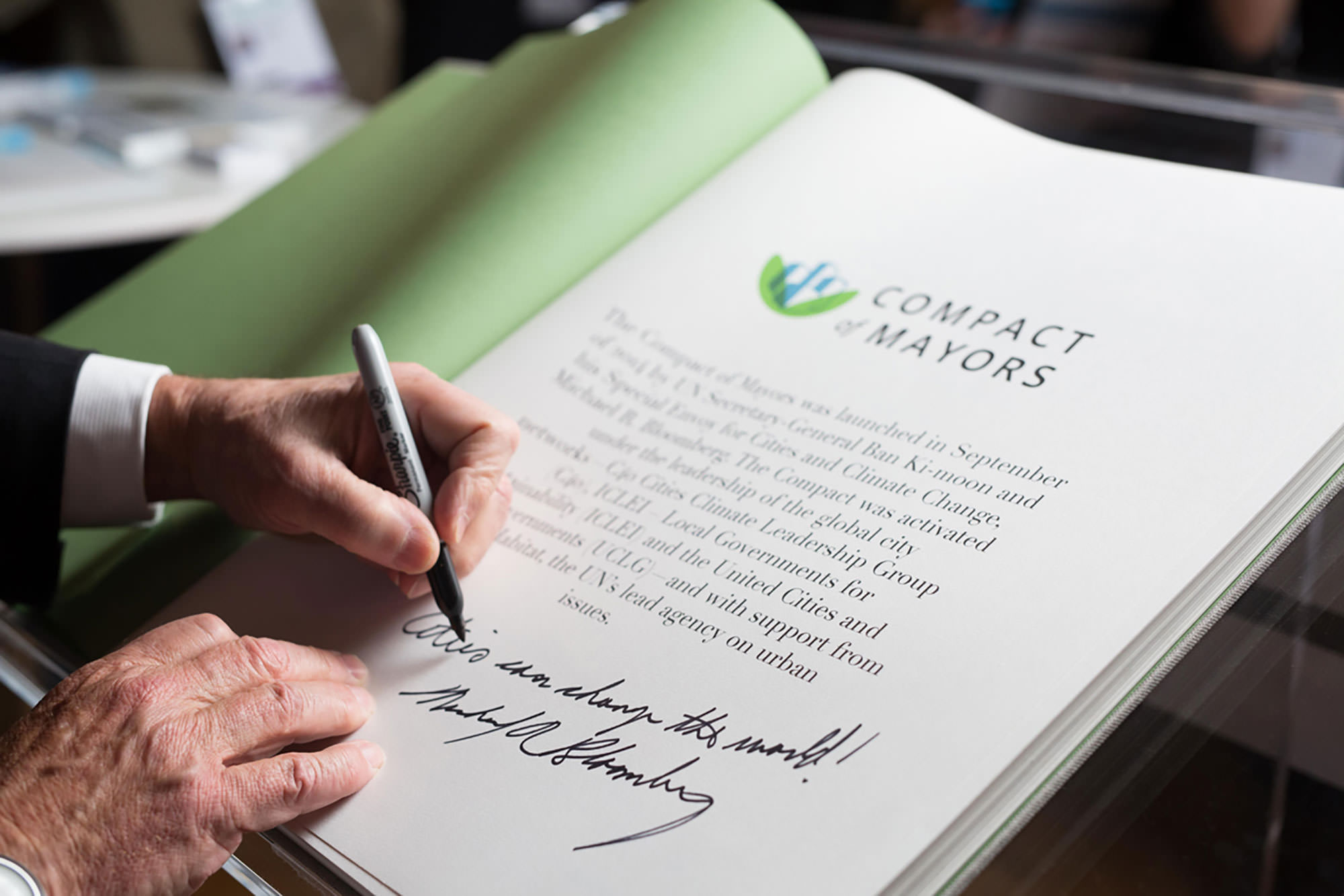 Mike Bloomberg signs the Compact of Mayors commitment book at the Climate Summit for Local Leaders in Paris