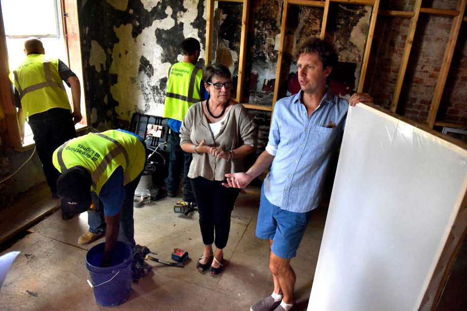 Lead architect Barbara Nelson, center, and lead artist Adam Frelin, right, talk about the installation of the Breathing Lights urban art project on Tuesday, Aug. 30, 2016 at 162 Clinton Ave. in Albany, N.Y. All Mighty General Contractors are installing the light panels. (Cindy Schultz / Times Union)