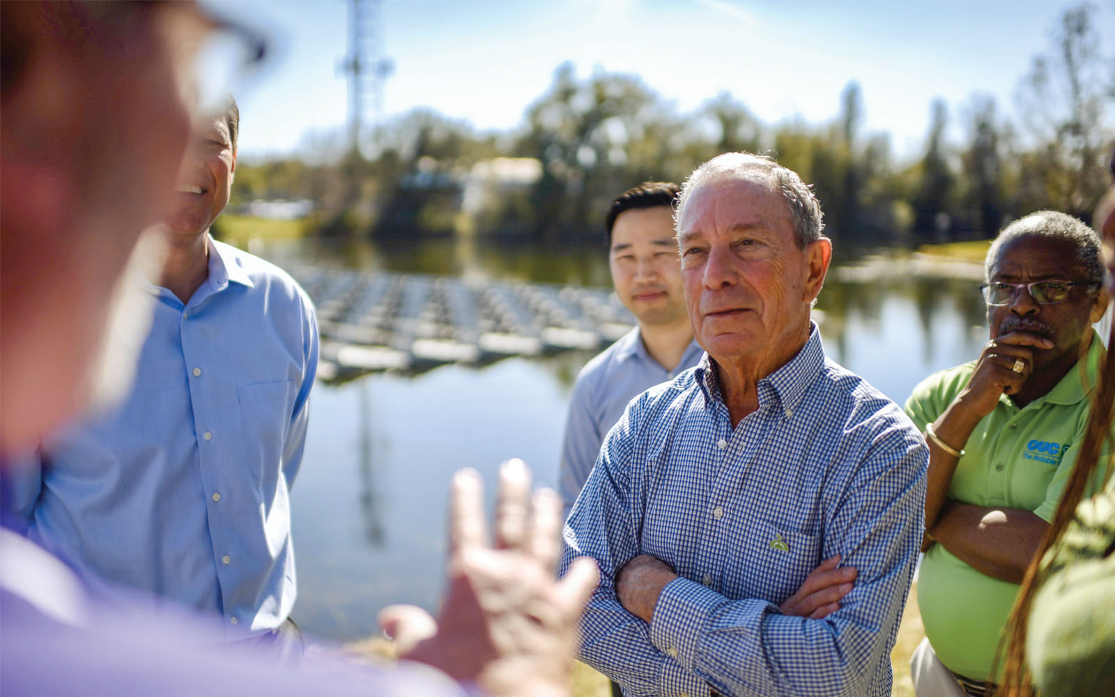 Mike Bloomberg visiting an energy utility with floating solar panels on a pond in Orlando, Florida, a winning city in the American Cities Climate Challenge.