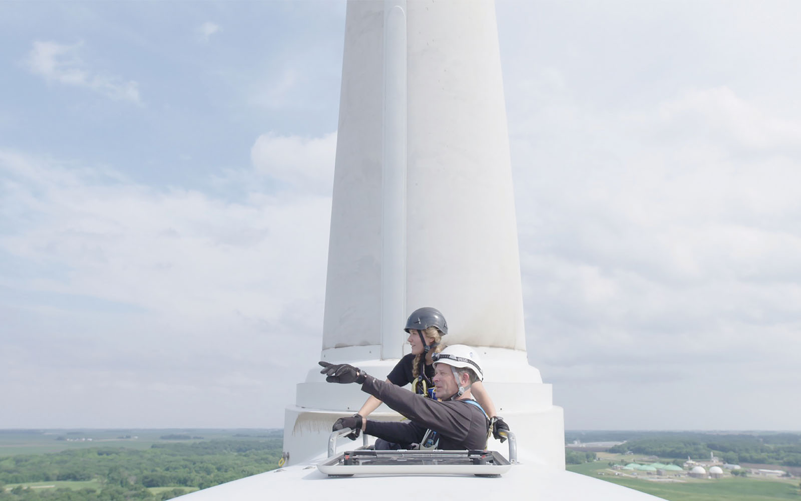 A community college student in Iowa studying wind energy, who is featured in Paris to Pittsburgh, looks out from the top of a turbine with her father.