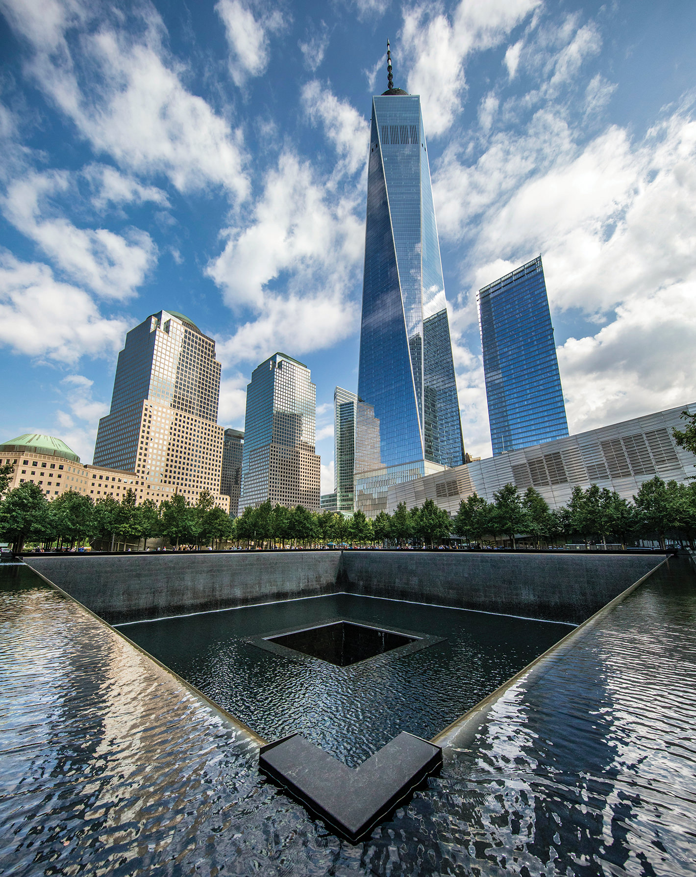 The One World Trade Center building rises above the reflecting pools at the 9/11 Memorial in Lower Manhattan.