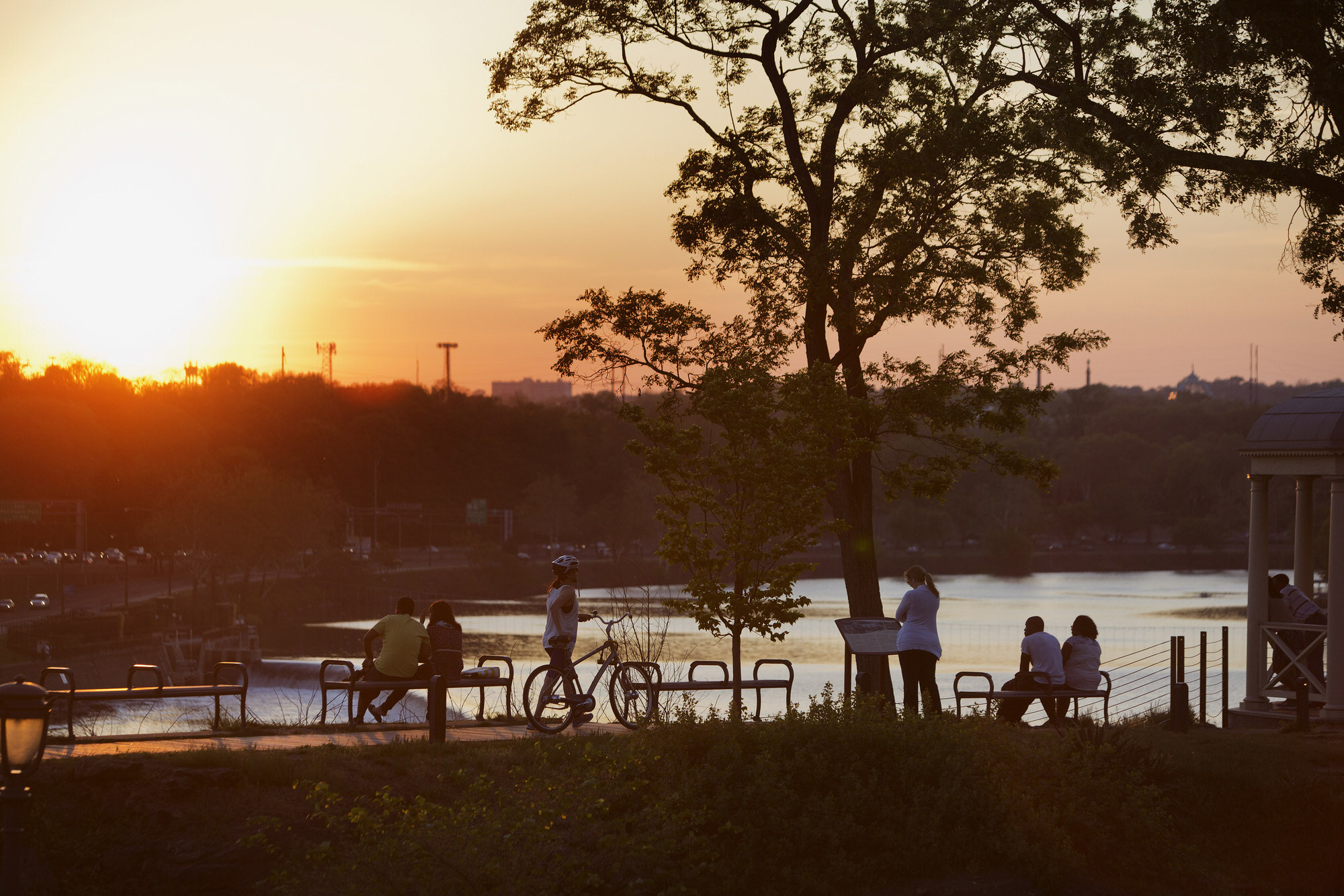 People watch the sunset over the Schuylkill River in Philadelphia, Pennsylvania, U.S., on Friday, May 8, 2015. Philadelphia, the largest city in the Commonwealth of Pennsylvania, is the center of the state's economic activity as well as home to seven Fortune 1000 companies. Photographer: Victor J. Blue/Bloomberg