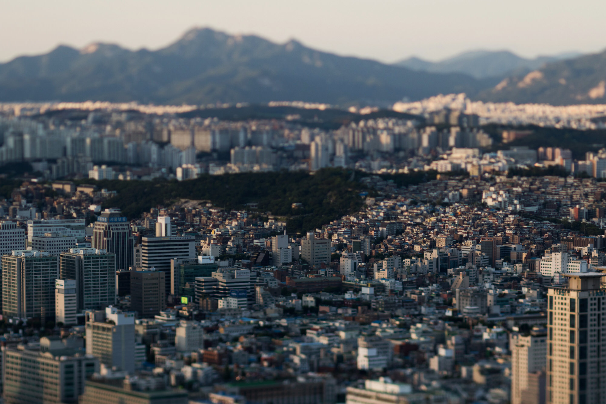 Buildings stand in this photograph taken with a tilt-shift lens in Seoul, South Korea, on Thursday, July 16, 2015. A report on July 23 may show that South Korea's economy expanded 2.3 percent in the second quarter, which would be the slowest pace in more than two years, according to the median estimate in a Bloomberg survey. Photographer: SeongJoon Cho/Bloomberg
