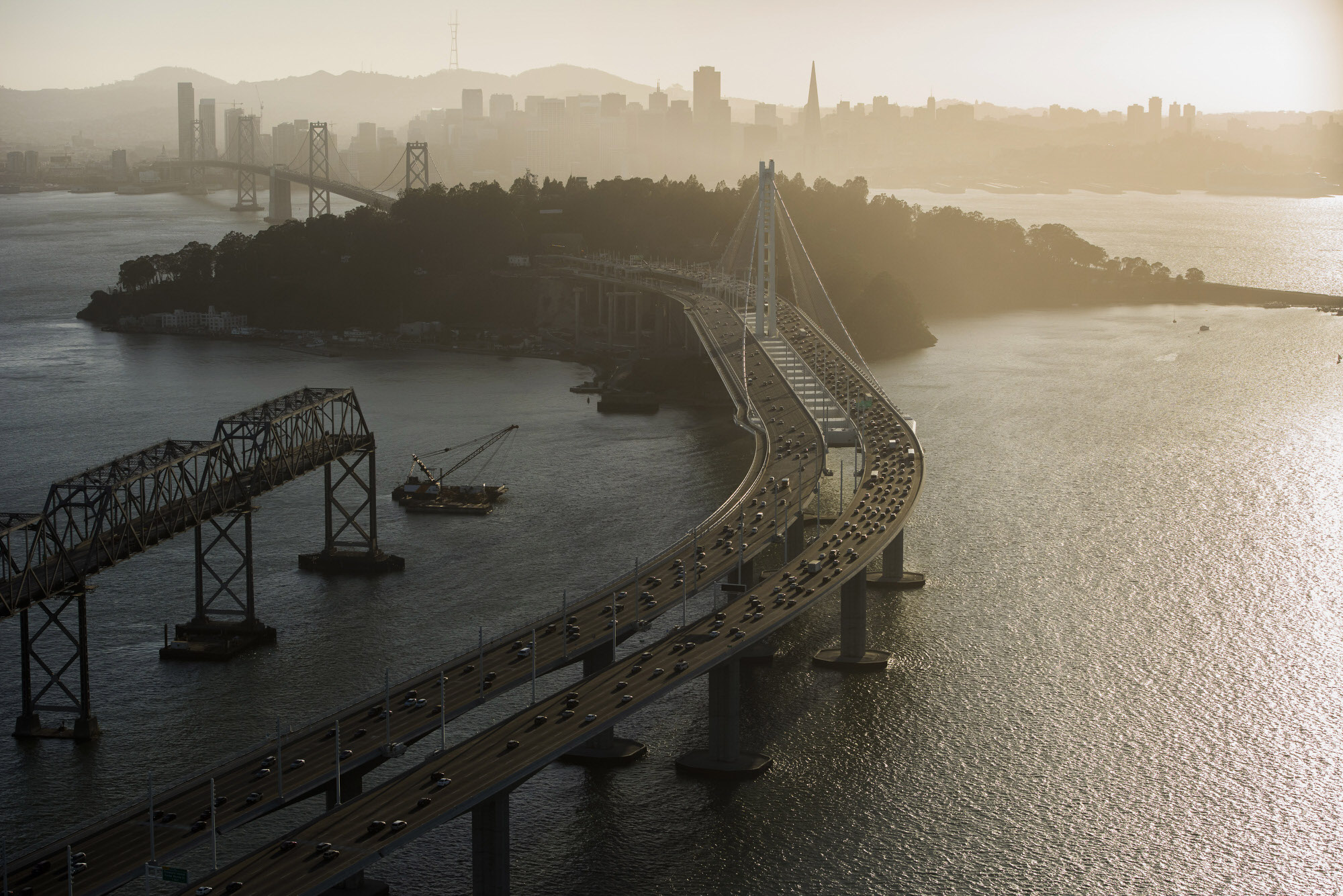 Cars travel over the San Francisco-Oakland Bay Bridge towards Treasure Island in this aerial photograph taken above San Francisco, California, U.S., on Monday, Oct. 5, 2015. With tech workers flooding San Francisco, one-bedroom apartment rents have climbed to $3,500 a month, more than in any other U.S. city. Photographer: David Paul Morris/Bloomberg