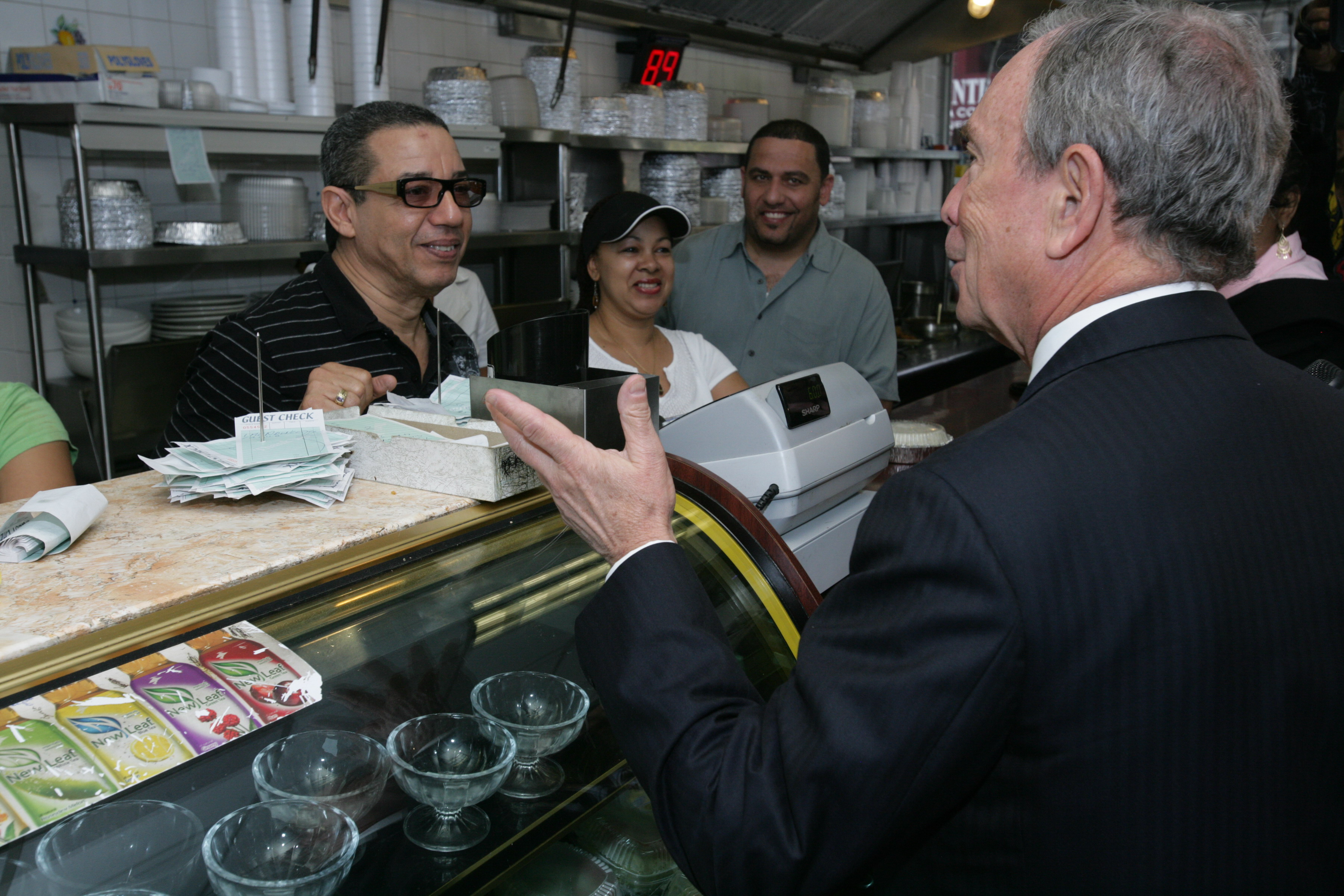 Mike speaks with employees at a local business in Washington Heights in New York City