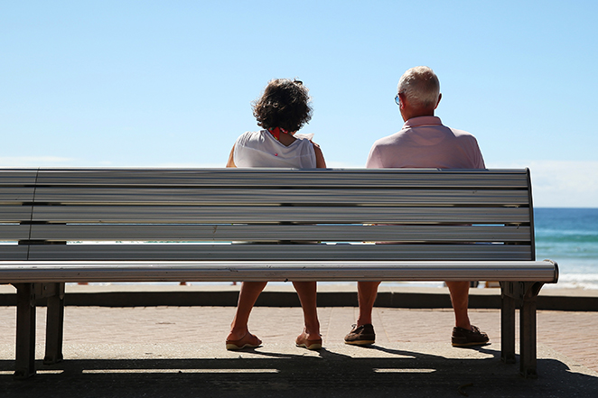 A woman and a man look out towards the beach while sitting on a bench in Sydney, Australia, on Wednesday, April 1, 2015. The number of people in Australia aged 65 and over is expected to double by 2055. Photographer: Brendon Thorne/Bloomberg
