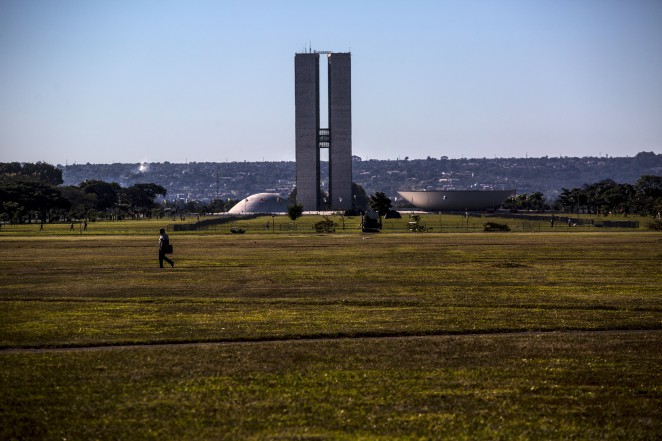 A man walks in a field in front of Congress in Brasilia, Brazil, on Friday, April 15, 2016. Brazil's lower house of Congress started a marathon session that will lead to a crucial impeachment vote on Sunday, following months of intense debate that has left Latin America's largest nation deeply divided. Photographer: Dado Galdieri/Bloomberg