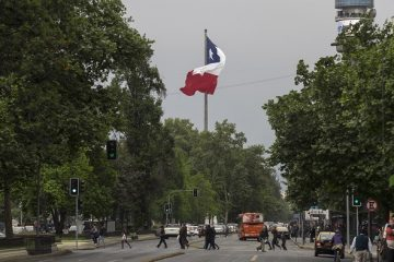 The Chilean flag flies as pedestrians cross a road in Santiago, Chile, on Saturday, Oct. 15, 2016. Chile's central bank will probably keep its benchmark rate at 3.5 percent for a 10th straight meeting as inflation slows to within policy makers' target range amid tepid economic growth. Photographer: Luis Enrique Ascui/Bloomberg