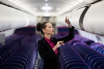 A flight attendant closes an overhead luggage compartment on-board a passenger aircraft operated by Wizz Air Holdings Plc at Liszt Ferenc airport in Budapest, Hungary, on Monday, Jan. 9, 2016. Wizz Air, the No. 1 no-frills carrier in Eastern Europe, grew passenger numbers 19 percent to 23 million as it added more destinations in the west of the continent. Photographer: Akos Stiller/Bloomberg