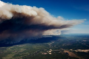 Huge plumes of smoke rise into the air as an out of control wildfire burns near Fort McMurray, Alberta, Canada, on Friday, May 6, 2016. The wildfires ravaging Canada's oil hub in northern Alberta have rapidly spread to an area bigger than New York city, prompting the air lift of more than 8,000 evacuees as firefighters seek to salvage critical infrastructure. Photographer: Darryl Dyck/Bloomberg