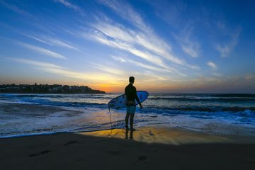 A surfer stands at the water's edge with his surfboard during sunrise at Bondi Beach in Sydney, Australia, on Monday, Jan. 23, 2017. Australia is leading a push to salvage a Pacific trade deal after U.S. President Donald Trump formally withdrew as a signatory to the 12-nation accord. Photographer: Dallas Kilponen/Bloomberg