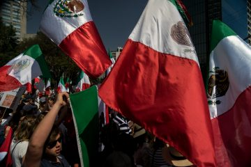 Demonstrators hold Mexican flags during a protest to demand the Mexican government defend the country in the face of U.S. President Donald Trump's threats to economic policy in Mexico City, Mexico, on Sunday, Feb. 12, 2017. Mexico's economy is facing the prospect of low growth and high inflation thanks in part to Trump's threats to economic policy to renegotiate free trade in North America and slap a tax on companies that send jobs south of the border. Photographer: Cesar Rodriguez/Bloomberg