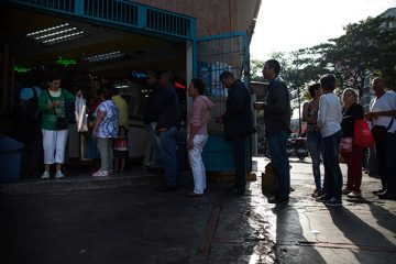 Customers line up to buy bread outside a bakery in Caracas, Venezuela, on Friday, March 17, 2017. Venezuelan bakeries are the latest industry to find themselves in the cross-hairs of President Nicolas Maduro's administration as bread lines grow in the capital Caracas. The government has ordered bakers to use scarce supplies of flour to produce price-controlled loaves and said that only 10 percent can be used to make the unregulated, pricey treats loved by Venezuelans. Photographer: Wil Riera/Bloomberg