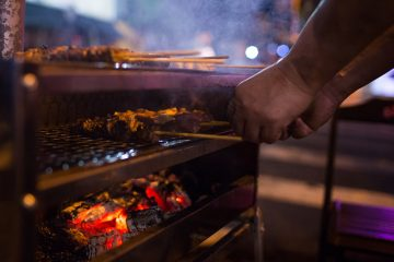 A street vendor grills meat in Sao Paulo, Brazil, on Friday, March 17, 2017. Federal authorities announced Friday they're investigating evidence that companies including JBS SA and BRF SA, the nation's largest meat producers, bribed government officials to approve the sale and export of soiled meat. Photographer: Victor Moriyama/Bloomberg