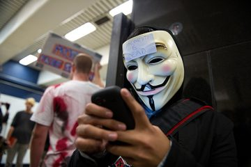 A demonstrator wearing a Guy Fawkes mask sends a text message as he joins the group Anonymous as they demonstrate in the Civic Center BART station in San Francisco, California, U.S., on Monday, Aug. 15, 2011. The protest followed BART's move on Aug. 11 to temporarily restrict mobile-phone service on its train platforms in San Francisco in an effort to ward off any protests.  Photographer: David Paul Morris/Bloomberg