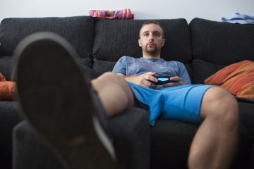 Alberto Gracia, a Spanish hospital orderly, sits on a sofa and plays video games at his home in Zaragoza, Spain, on Tuesday, Sept. 9, 2014. Gracia's finished 545 hours of online courses on the Spanish medical system, learning about hygiene, medical equipment and hospital-room layout. Photographer: Angel Navarrete/Bloomberg *** Local Caption *** Alberto Gracia