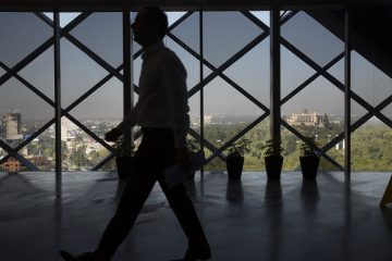 The silhouette of a man is seen as he walks on a floor of the BBVA Bancomer building with a view of Chapultepec Castle, back right, in Mexico City, Mexico, on Wednesday, Sept. 9, 2015. The skyscraper is nearing completion as a decade-long building spree threatens to leave Mexico City with a large surplus of office space due to a fall in oil prices that has slowed the economy. Photographer: Susana Gonzalez/Bloomberg