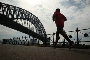 A man runs past the the Sydney Harbour Bridge in Sydney, Australia, on Friday, April 29, 2016. Australia's drive to balance the books will see the federal government's debt pile top out within about five or six years and then start to shrink again, according to Treasurer Scott Morrison. Photographer: Brendon Thorne/Bloomberg