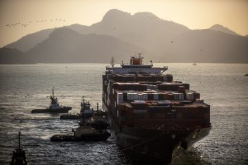 """Tugboats assist the Hapag-Lloyd Holding AG Prague Express container ship dock at the Cia Siderurgica Nacional SA (CSN) Sepetiba Tecon terminal inside the Port of Itaguai in Rio de Janeiro, Brazil, on Friday, Aug. 19, 2016. Brazil's government will launch a PR campaign following the Olympics in Rio to create an image of """"credibility"""" after prolonged economic and political crisis, country's chief export official says in interview. Photographer: Dado Galdieri/Bloomberg"""