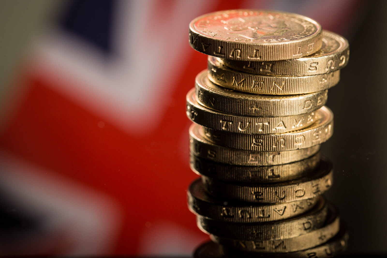 A stack of British one pound sterling coins stand in front of a British Union flag, also known as a Union Jack, in this arranged photograph in Guildford, U.K., on Monday, June 13, 2016. Sterling swung on Monday as anxiety about Britain's referendum on staying or leaving the European Union continued to build. Photographer: Jason Alden/Bloomberg