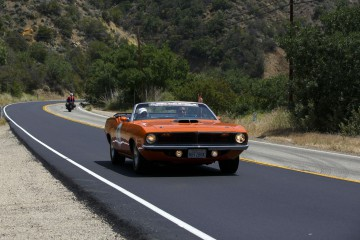 Jay Jeffs and Sara Jeffs drive a 1970 Plymouth Cuda convertible drives during the Friends of Steve McQueen Car Show Rally from Camarillo to the Pine Mountain Summit, California, U.S., on Saturday, May 14, 2016. Dozens of vintage Porsches, Alfa Romeos, and other classics covered 70 miles along Southern California's most picturesque roads, all to benefit the school for wayward boys that McQueen had attended as a youth. Photographer: Patrick T. Fallon/Bloomberg