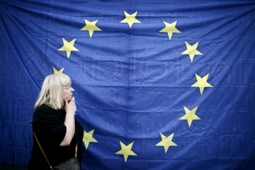 A woman walks in front of a European Union (EU) flag during a pro European Union (EU) demonstration in Thessaloniki, Greece, on Monday, June 22, 2015. After a day of talks on Monday, leaders from Greece's 18 fellow euro-zone countries agreed that Greek Prime Minister Alexis Tsipras's government was finally getting serious after it submitted a set of reform measures that began to converge with the terms demanded by creditors. Photographer: Konstantinos Tsakalidis/Bloomberg